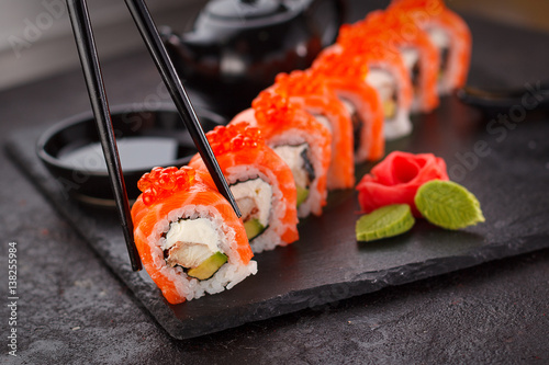 Foto op Aluminium Sushi bar Japanese cuisine. Salmon sushi roll in chopsticks on a stone plate over concrete background.