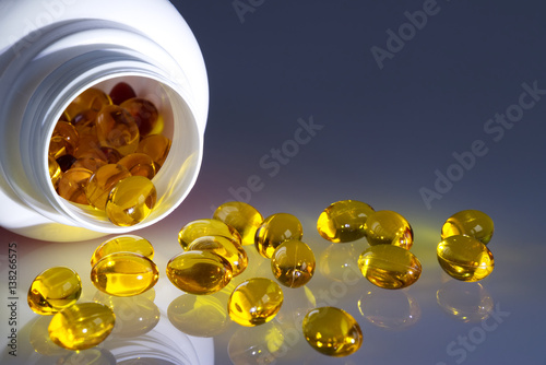 Fotografie, Obraz  Omega 3 fish oil capsules spilled from a plastic bottle on a gradient background