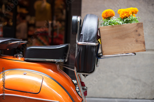 Orange Scooter with Orange Marigolds in Wooden box.