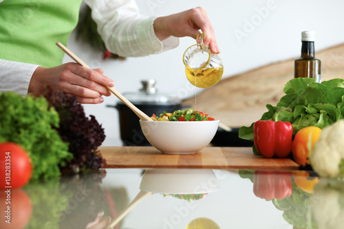 Poster Cuisine Closeup of human hands cooking vegetables salad in kitchen on the glassr table with reflection. Healthy meal and vegetarian concept