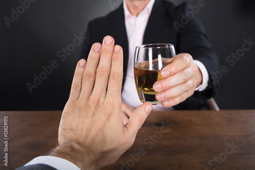 Spoed Foto op Canvas Bar Businessman Hand Rejecting A Glass Of Whiskey