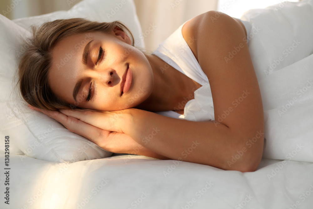 Fototapeta Beautiful young woman sleeping while lying in bed comfortably and blissfully. Sunbeam dawn  on her face