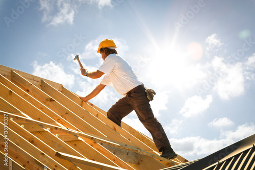 Obraz roofer or Carpenter working on Roof on construction site backlit - fototapety do salonu