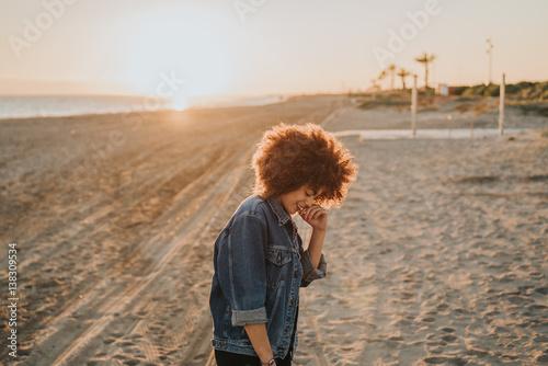 Chica feliz en la playa con el atardecer