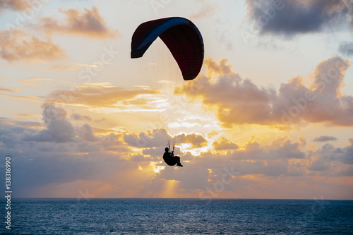 Person on parachute in sunset