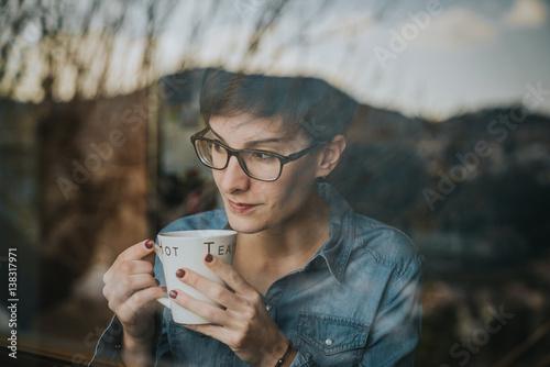 Chica mirando por la ventana con el té