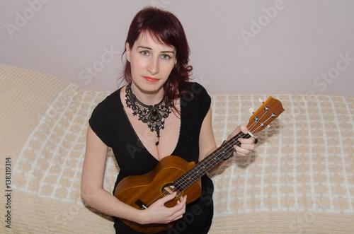 Valokuva  Ritratto di una giovane musicista che suona l'ukulele