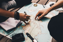Couple Planning Vacation Using The World Map.