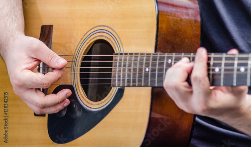 Fotografia, Obraz Musician's hands plays a chord on a yellow acoustic guitar