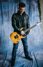 Man In Black Jacket Poses With Electric Guitar On Blue Cloth