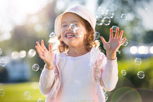 Adorable Little Girl, Has Happy Fun With Cheerful Smiling Face. Carefree Child Laughing, Running And Jumping On Green Summer Meadow, Catching Soap Bubbles. Happiness, Childhood And Freedom Concept.