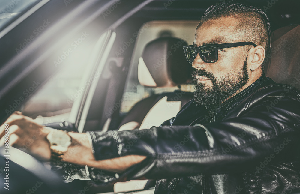 Photo  Handsome brutal young man behind the wheel of a luxury car