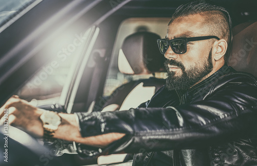 Poster  Handsome brutal young man behind the wheel of a luxury car