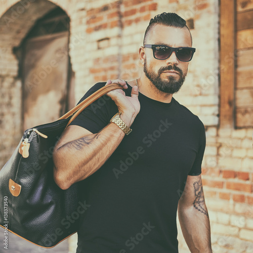 Handsome man with beard wearing sunglasses and holding black bag Canvas Print