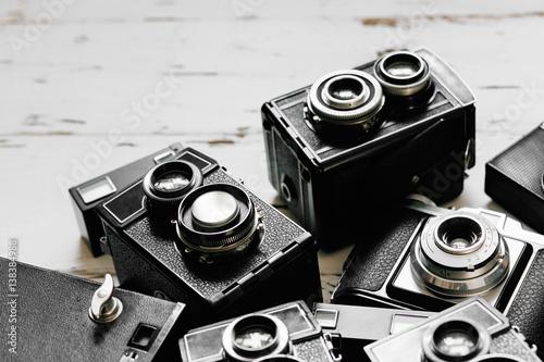 Stampa su Tela  old vintage retro photo cameras on white wooden background