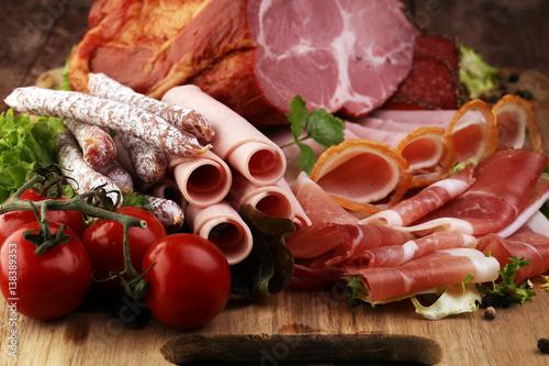 Fototapeta Tacka na jedzenie z pysznym salami, kawałki plasterki szynki, kiełbasa, pomidory, sałatka i warzywo - Talerz mięsa z wyborem