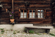 Facade Of Old Wooden House With Windows And Bench In Traditional  Swiss Village