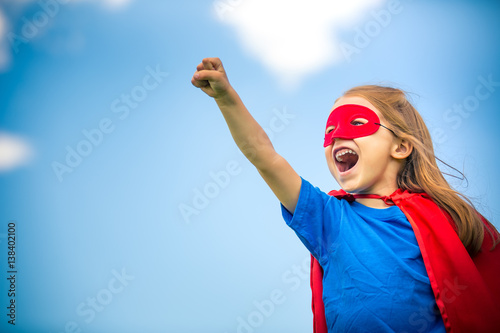Fototapeta Funny little girl plaing power super hero over blue sky background. Superhero concept. obraz