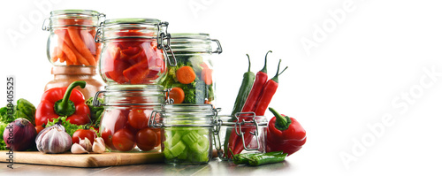 Foto op Plexiglas Verse groenten Jars with marinated food and raw vegetables isolated on white