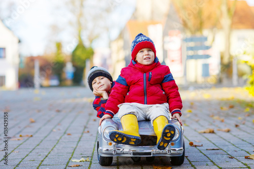 Two little kids boys playing with toy car, outdoors