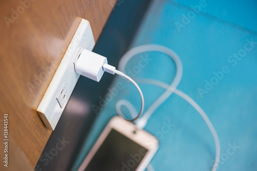 Fotografia Charging smart phone in public place and smart phone place on the blue floor in selective focus