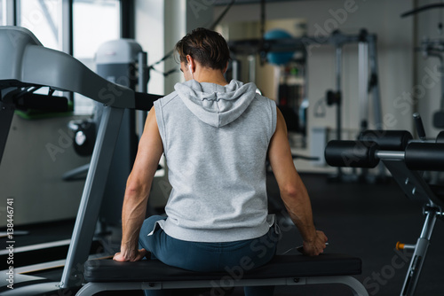 Fitness man wearing sportswear resting after working out and sitting on bench in gym