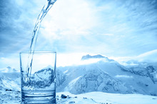 Concept Purity Of Blue Water In Transparent Glass Over Winter Landscape Of Mountains Higher Than Clouds, Close Up