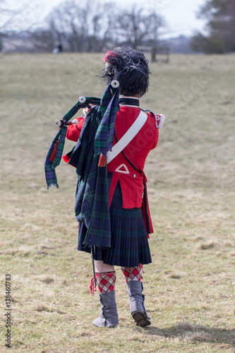 Scottish highland piper on the field with bagpipes