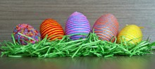Easter Multicolored Decorative Eggs With Wrapped Yarn In Green Grass Nest On Wooden Background, Close Up. Easter Decoration.