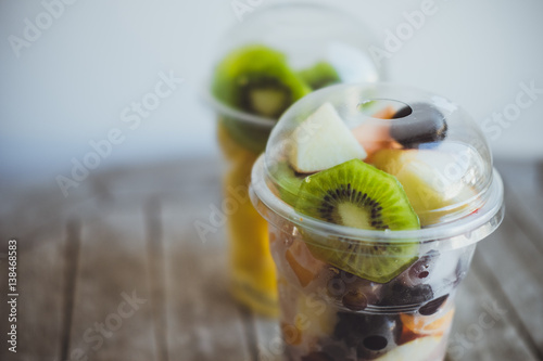 Fresh Fruits in Plastic Cups for takeaway: kiwi, pineapple, tangerines, apples, melon in plastic cups on the wooden table