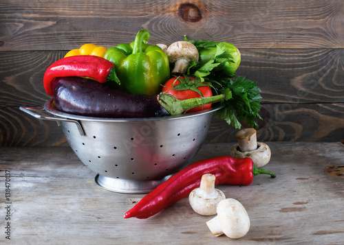 Staande foto Hot chili peppers Fresh vegetables tomato, zucchini, eggplant, sweet pepper, hot pepper metal colander wooden table