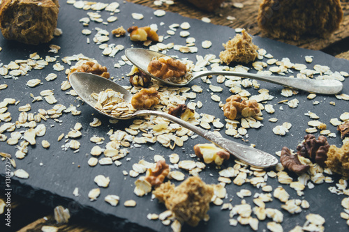Foto op Aluminium Scandinavië Two vintage spoons different shapes on the slate Board, scattered with oatmeal, walnuts and bread crumbs