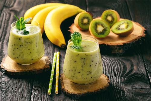 Banana and kiwi smoothie on dark wooden background.