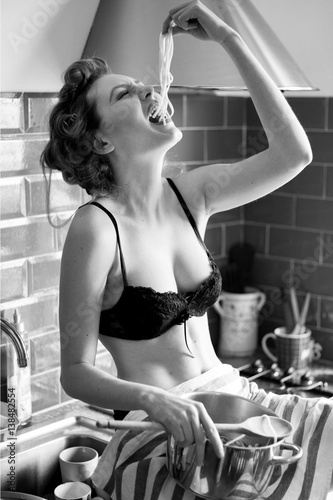 Leinwand Poster Bellissima ragazza mangia spaghetti con le mani in cucina