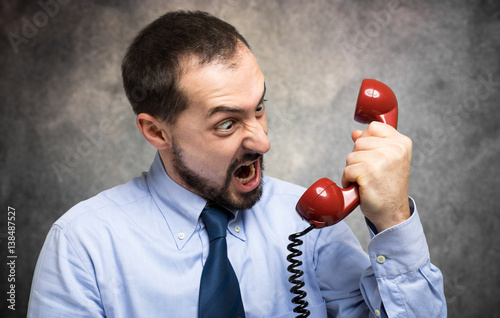 Businessman yelling at his phone in his office Fototapet