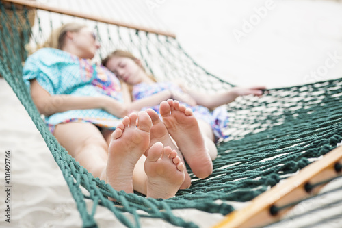 Fotografie, Obraz  Barefoot and Relaxed family napping in a hammock together outdoors on a sunny day