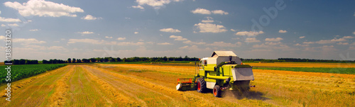 Foto  Combine harvester harvesting wheat during harvest on sunny summer day