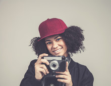 Portrait Of Pretty African Smileing Young Teenage Hipster Woman Model With Retro Photo Camera Wearing A Pink Hat, Black Leather Jacket. Fashion Look.