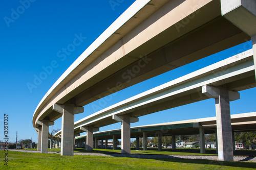 Highway overpass crossing neighborhood with a blue sky background Wallpaper Mural