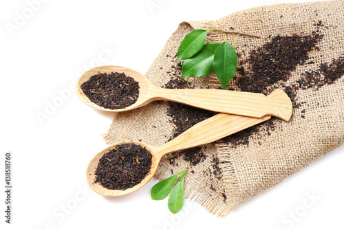 Black tea in wooden spoons isolated on white