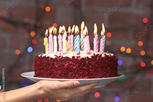 Female Hand Holding Plate With Tasty Birthday Cake Against Defocused Lights