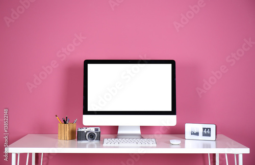 Computer display on white table against color wall - 138522148