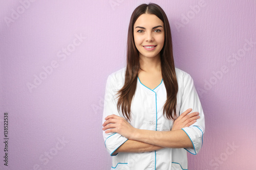 Young specialist in beauty salon against color wall