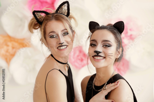 Fotografie, Obraz  Beautiful young women with cat makeup and ears at party