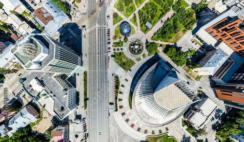 Fototapeten New York Aerial city view with crossroads, roads, houses, buildings, parks and parking lots. Copter drone helicopter shot. Panoramic wide angle image.
