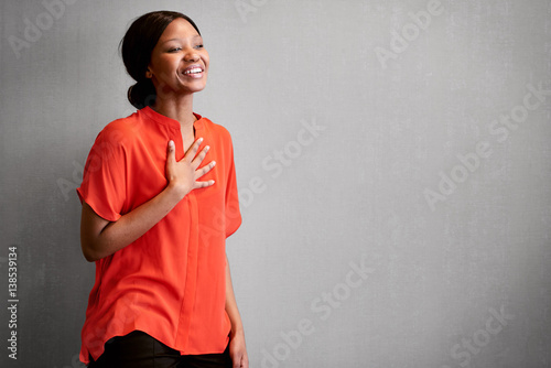 Fotografia  Black female business person busy laughing with one hand against her chest while wearing a bright colourful orange blouse with space for copy text on the right of the image