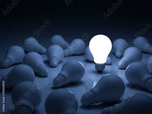 Fototapeta One glowing light bulb standing out from the unlit incandescent bulbs with reflection , leadership and different creative idea concept