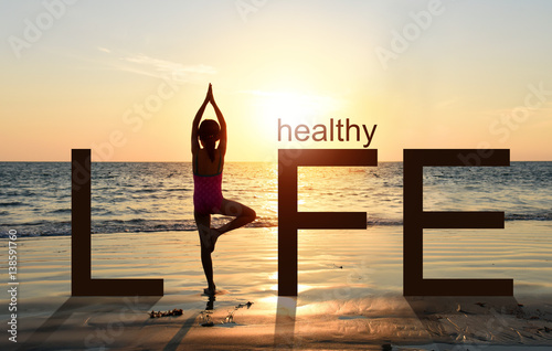 Fototapeta Silhouette of A girl practicing Yoga vrikshasana tree pose on tropical beach with sunset sky background, watching the sunset, standing as a part of the wording concept for healthy life.  obraz
