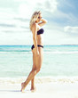 Beautiful woman in black swimsuit. Young and sporty girl posing on a beach at summer. Traveling, tourism, concept.