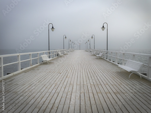winter view on empty pier covered with frost in perspective